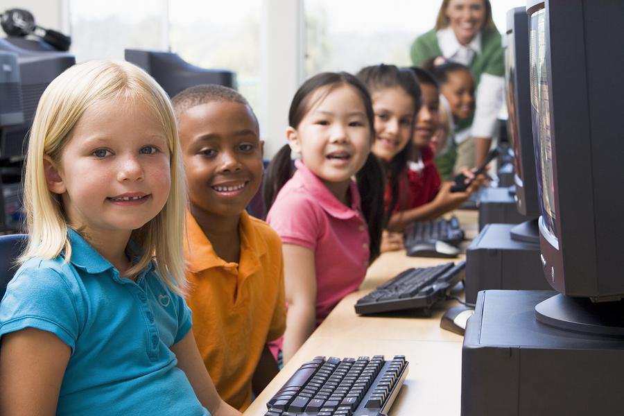 Children at computer terminals with teacher in background (depth